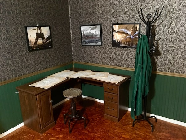 In-game: A desk with design schematics covering it.