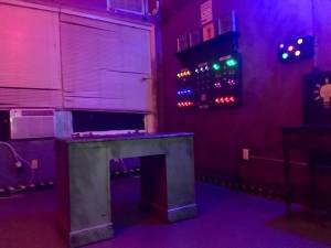 In-game: A desk in a dimly lit room, a panel with glowing switches in an assortment of colors.