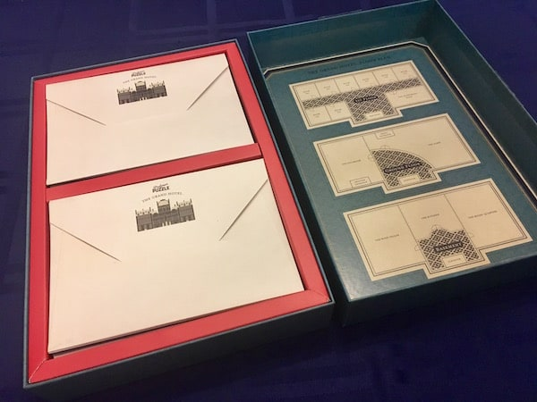 The opened box reveals stacks of invitations and a map of the hotel.
