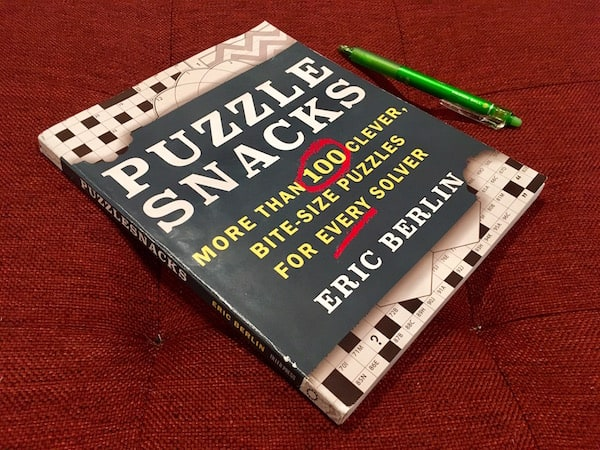 "Cover of Puzzle Snacks, ""More than 100 clever bite-sized puzzle for every solver"" by Eric Berlin."
