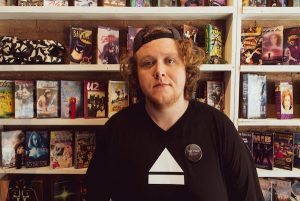 A person with an eject symbol on his shirt in front of a shelf of movies.