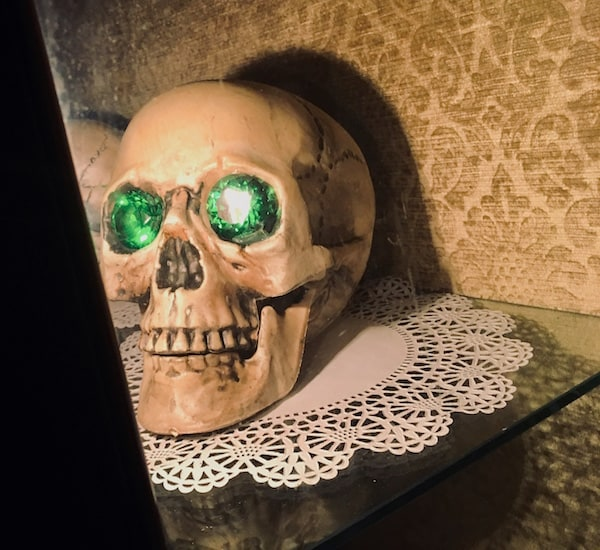 In-game: a human skull with emeralds in its eye sockets resting on a doily.
