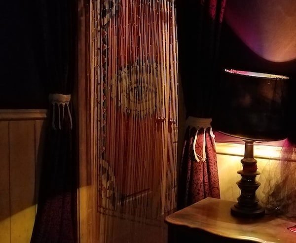 A table lamp next to a doorway with a beaded curtain featuring an open eye.