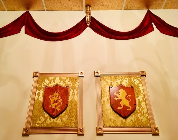 In-game: Two shields hung on a wall decorated in red velvet.