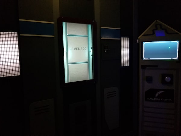 """In-game: A futuristic elevator with a doorway labeled """"Level 1"""""""