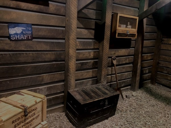 In-game: the approach to a mine shaft, the floor has trunks filled with mining gear.