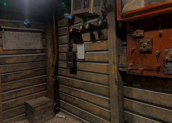 In-game: A wood walled mine with assorted mechanical interactions on the walls.