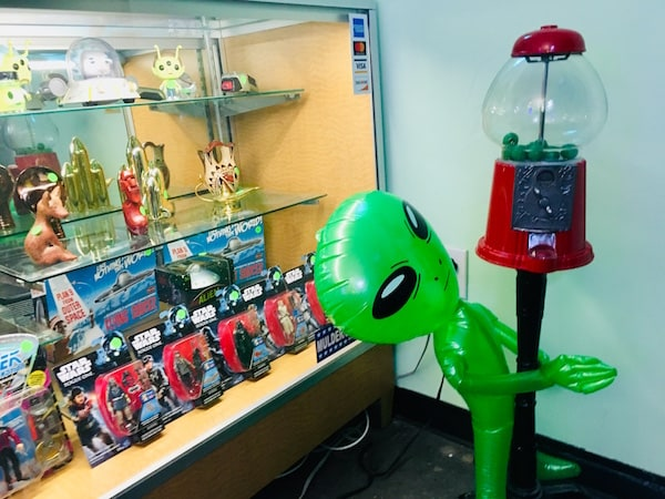 In-game: A class display filled with sci fi toys, and a gumball machine with a green inflatable alien hugging it.