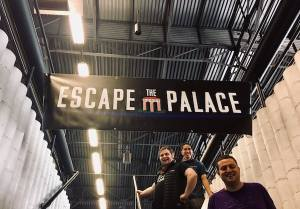 """An """"Escape the Palace"""" Banner hanginging over a stairwell with my team under it."""