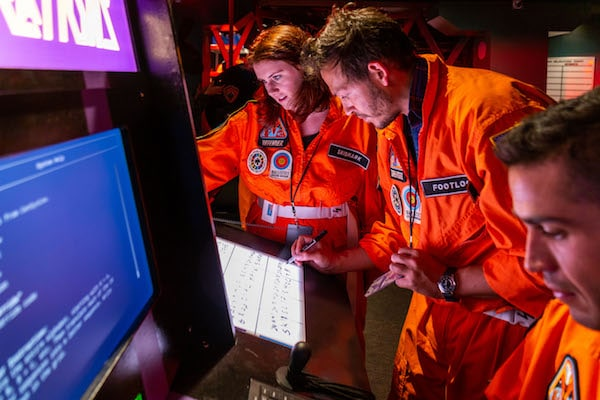 In-game: 3 orange flightsuited players working on a puzzle.