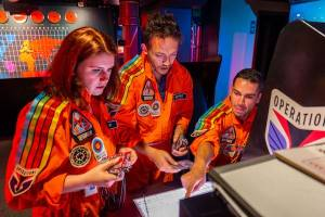 In-game: 3 players in orange flightsuits working at the Operations cabinet.