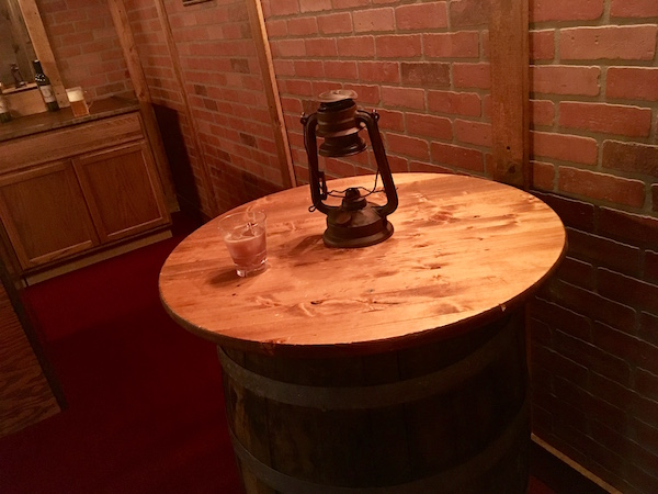 In-game: closeup of a small tabletop on a barrel with a drink and lantern atop it.