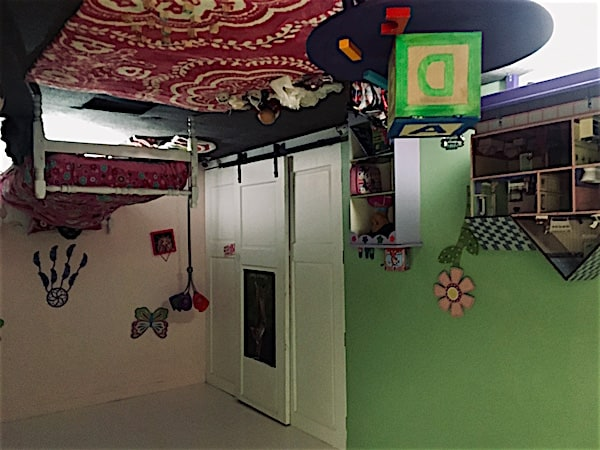 In-game: An upside down girl's bedroom with a bed, toys, and a dollhouse.