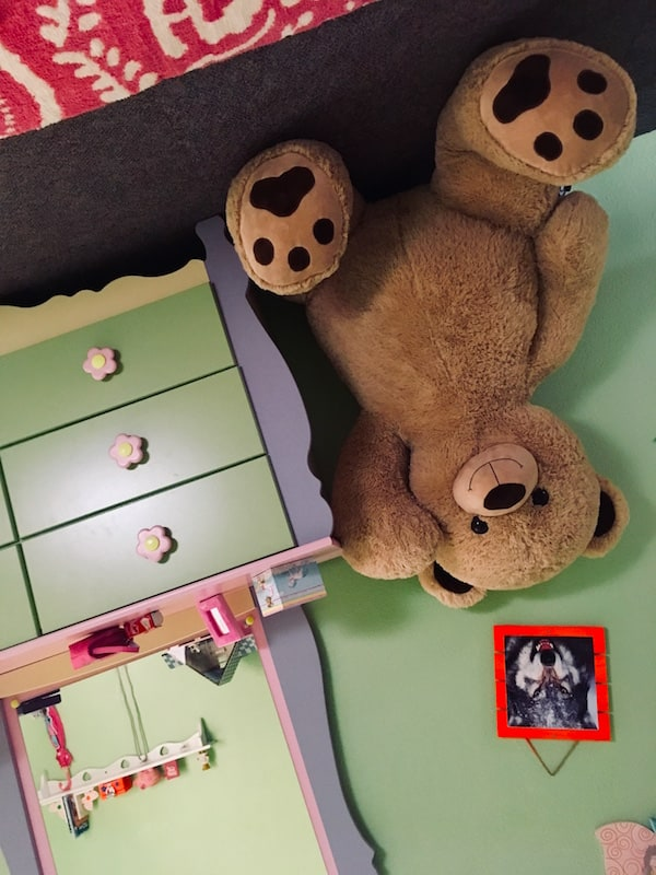 In-game: A girl's dresser and oversized teddy bear all upside down.