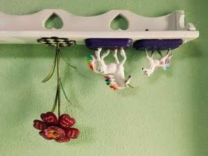In-game: An upside down shelf with a pair of unicorns and a flower.