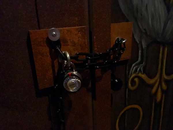 In-game: closeup of a doorway chained with a padlock.
