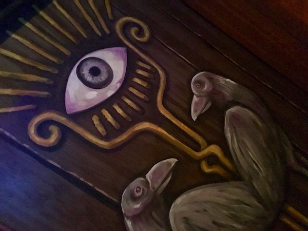In-game: closeup of a door pained with an eye and two ravens.