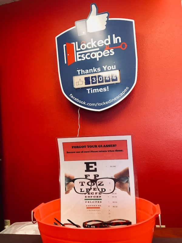 The Locked In Escapes logo above a bucket of loaner reading glasses.