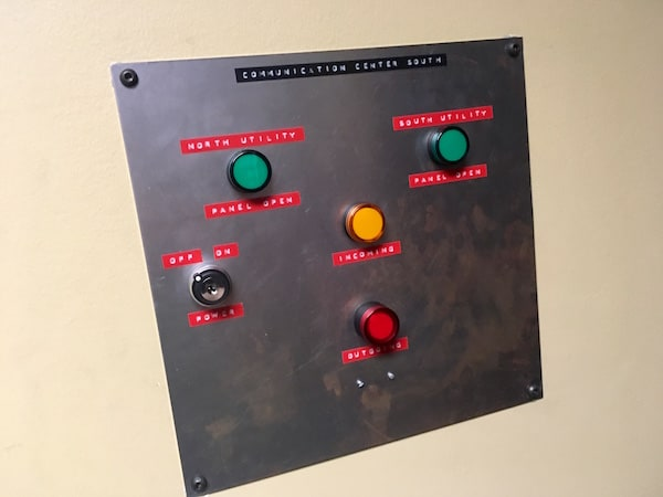 In-game: Closeup of a communications panel with multiple lights and a big red button.