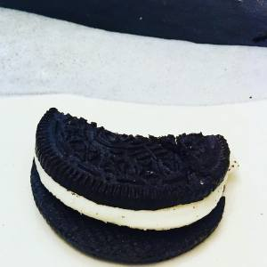 Closeup of a half eaten oreo on a plate.