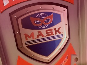 In-game: the MASK logo features a globe with a mask on it.