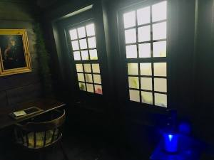 In-game: The stern of a ship, large windows illuminate the captain's study.