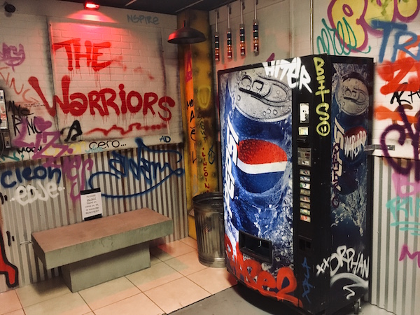 In-game: graphittied subway walls with a Pepsi vending machine.