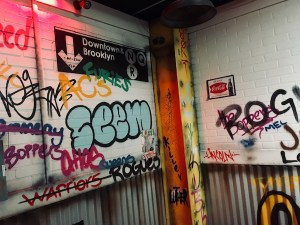 In-game: A NYC subway wall covered in graphitti and a sign for the NQR Downtown & Brooklyn.