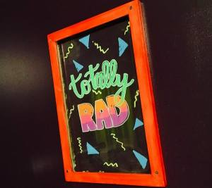 """In-game: A dry erase board in pright pastel colors reads, """"Totally RAD."""""""