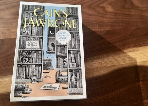 The box art for Cain's Jawbone depicts a library with a deadman on the floor and a person in the shadows outside of the window.