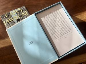 Cain's Jawbone's box open, it contains a stack of individual book pages.