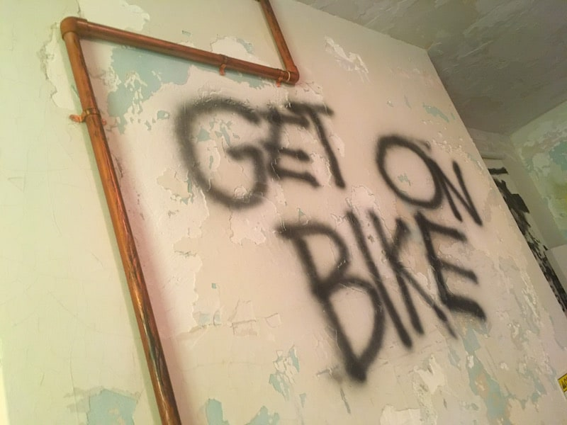 "In-game: ""GET ON BIKE"" is spray painted on an old plaster wall."