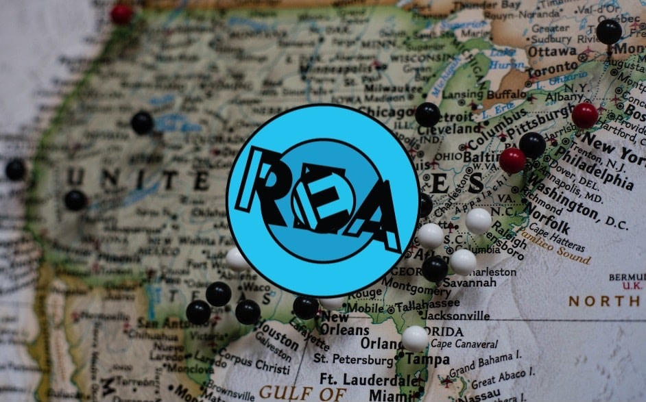 REA logo with a photo of a pinned map of the USA in the background.