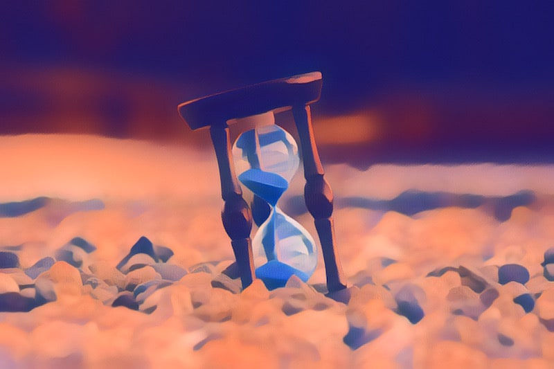 An hourglass with blue sand sitting atop pebbles.