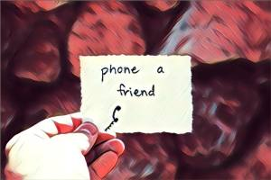 "A hand holding a handwritten note that reads, ""phone a friend."""