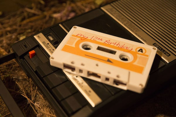 """A cassette tape labeled """"My 12th Birthday"""" sits on top of a tape recorder."""