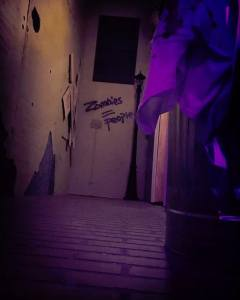 """In-game: an alleyway with """"zombies = people"""" painted on the wall."""