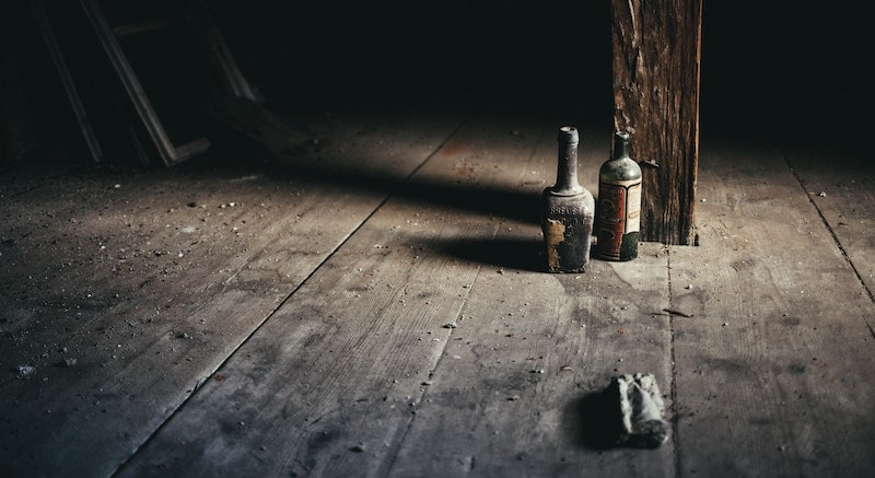 A dirty, dusty, dark room with a pair of old and open liquor bottles casting long shadows.