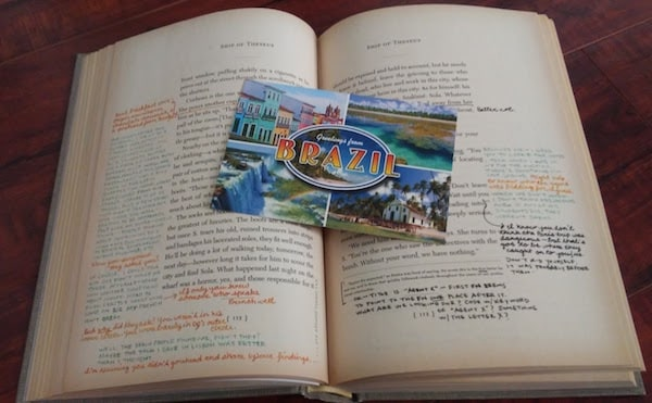 """Sample pages of Ship of Theseus, along with a postcard that says """"Greetings from Brazil."""""""