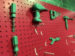 In-game: a red pegboard with green toy tools hanging from it.