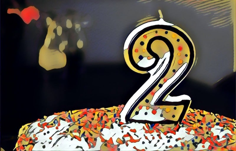 """Stylized image of a birthday a with a """"2"""" candle on it."""