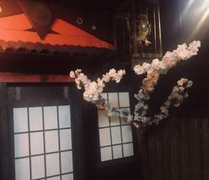 In-game: a japanese building with a cherry blossom out front.
