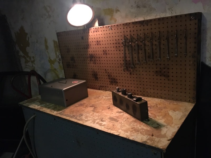 In-game: a workbench with wrenches hanging from a pegboard.