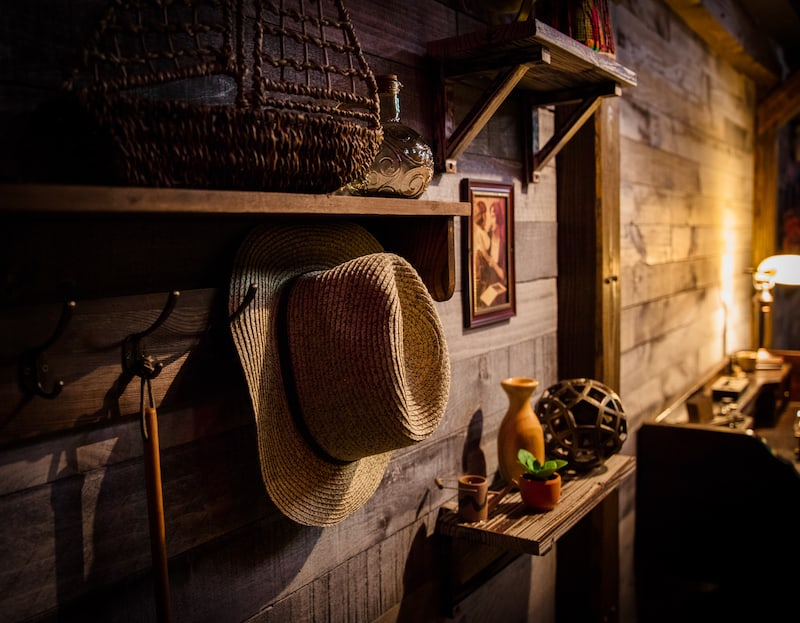 In-game: the wooden wall of a cabin with small shalves and hooks displaying many different trinkets.