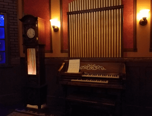 A grandfather clock stands next to an organ in a room lit by sconces.