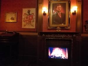 A man's portrait and other wall hangings lit by sconces over a digital fireplace.