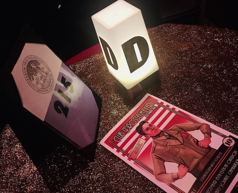 "In-game: A table with an illuminated ""D"", a table number and a Club Drosselmeyer comic."