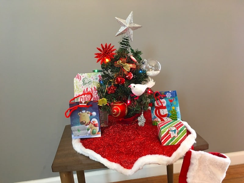 A tiny christmas tree with gifts gathered around it on a small table.