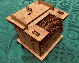 A wooden puzzle box with a spindle of gears.