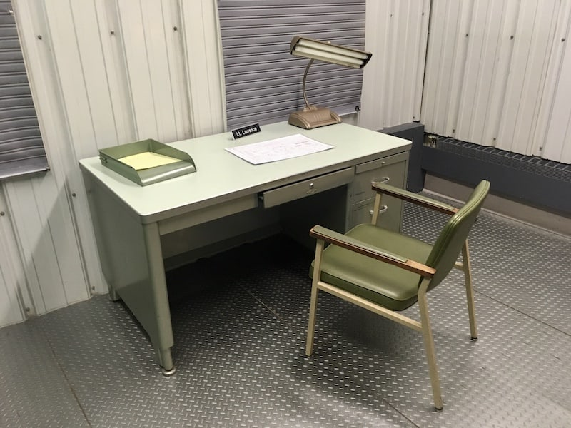 In-game: A metal desk in the middle of an old nuclear bunker.